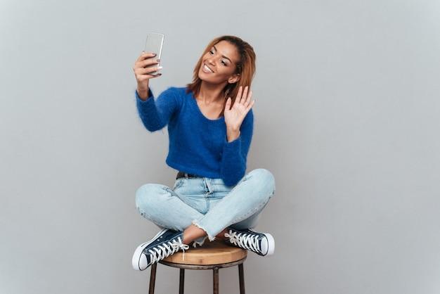 Schoonheid afrikaanse vrouw in blauwe trui en spijkerbroek selfie maken op stoel. geïsoleerde grijze achtergrond