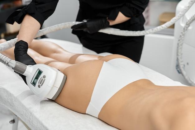 Schoonheid arts doet massage voor vrouwenbeen met professionele stimulator