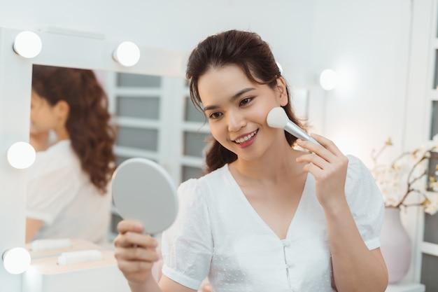 Schoonheid aziatische vrouw make-up toe te passen. mooi meisje en cosmetische met een grote borstel toe te passen op een gezellige slaapkamer interieur