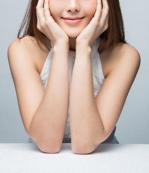 Schoonheid azië meisje glimlach zittend op een stoel en haar kin en wang met de hand aan te raken. portret van dromerige schattige jonge vrouw in kapsel rusten in studio