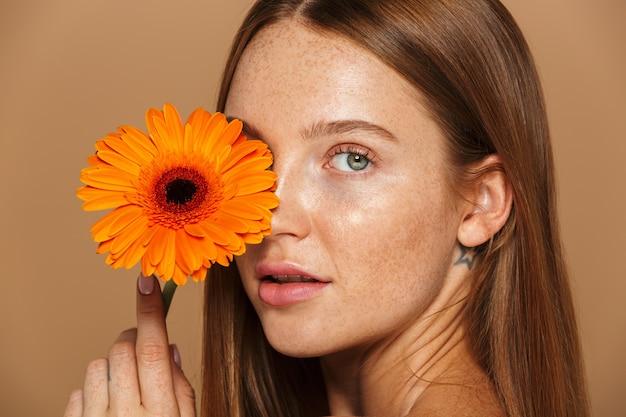 Schoonheid beeld van prachtige shirtless vrouw 20s permanent met oranje bloem, geïsoleerd op beige achtergrond