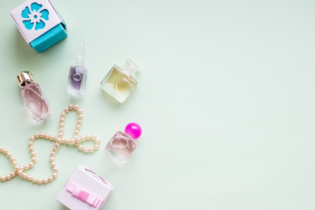 Schoonheid blog concept. accessoires, huidige dozen, cosmetica en sieraden op pastel groene muur. vrouwendag concept. gelukkige vrouwendag tekst teken. luxe dure sieraden en make-up