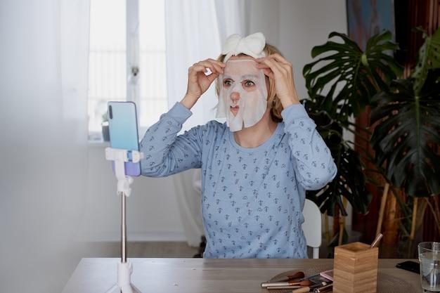 Schoonheid blogger meisje met een cosmetisch masker op haar gezicht online op een smartphone bloggen, uitzending en cosmetica concept