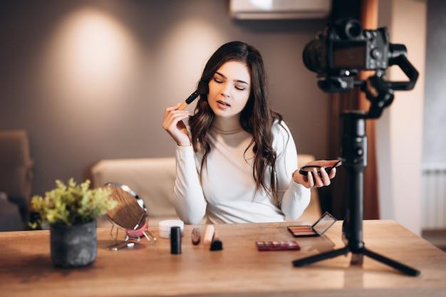 Schoonheid blogger mooie vrouw filmen dagelijkse make-up routine tutorial op camera. influencer jonge vrouw live streaming cosmetica product review in thuisstudio. vlogger baan. diy make-up aanbrengen.