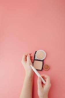 Schoonheid blogger vrouw handen met fles en buis spa professionele hi-end cosmetica op roze achtergrond, minimalisme concept, warme gezellige tonen en copyspace