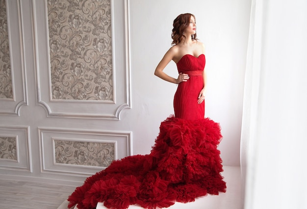 Schoonheid brunette model vrouw in rode avondjurk. mooie mode luxe make-up en kapsel