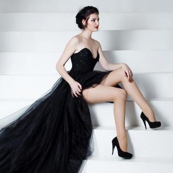 Schoonheid brunette model vrouw vakantie make-up zittend op de trap.