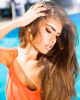 Schoonheid brunette portret van meisje bij zwembad in goede vorm met lang donker haar en tan huid rode lippen met cat eye, neon make-up oogschaduw en glimlach