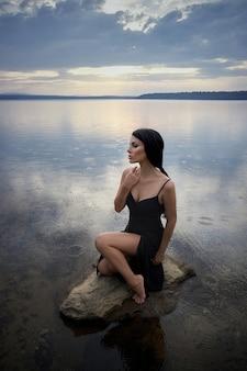 Schoonheid brunette vrouw in een zwarte jurk poseert in een zeemeer tegen een blauwe hemelachtergrond. lang haar sexy vrouw en mooie schoonheidsmake-up op haar gezicht
