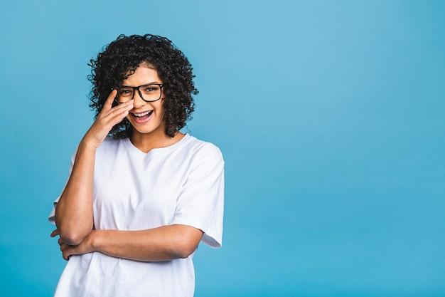 Schoonheid close-up portret van jonge afro-amerikaanse meisje met afro haar. meisje dat camera bekijkt. geïsoleerd op blauwe achtergrond.