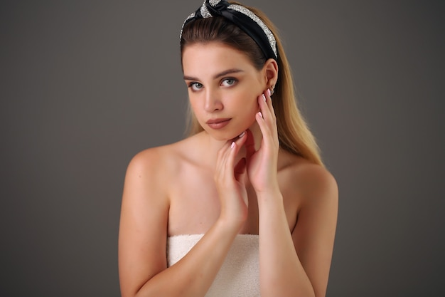 Schoonheid close-up portret van mooi, fris en gezond meisje over grijze achtergrond.