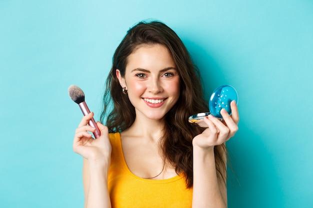 Schoonheid. close-up van aantrekkelijke stijlvolle vrouw die make-up aanbrengt, borstel en schattige zakspiegel vasthoudt, tevreden glimlacht naar de camera, staande over blauwe achtergrond.