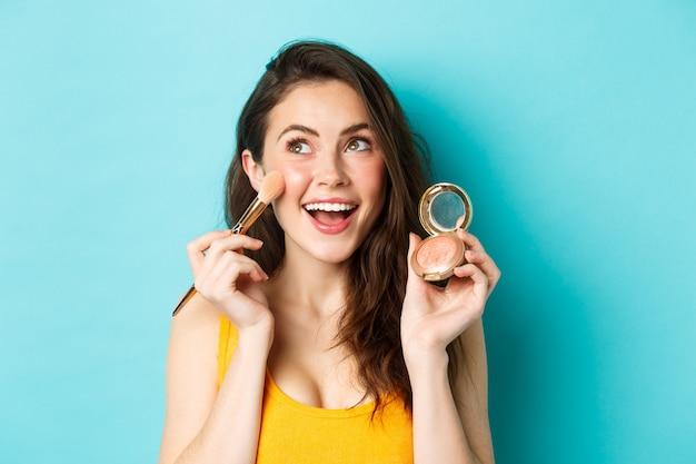 Schoonheid. close-up van een mooie jonge vrouw die naar de linkerbovenhoek kijkt en glimlacht terwijl ze bloost op de wangen met een make-upborstel, blij tegen een blauwe achtergrond.