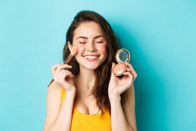 Schoonheid. close-up van mooie jonge vrouw sluit de ogen en glimlacht terwijl ze blos op de wangen aanbrengt met een make-upborstel, blij tegen een blauwe achtergrond
