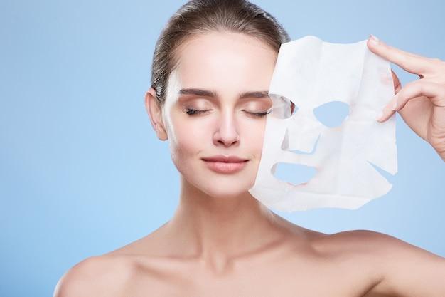 Schoonheid concept, hoofd en schouders van meisje masker verwijderen uit gezicht, gezicht pack. jonge vrouw met zuivere huid, gesloten ogen en glimlachen. studio, grijze achtergrond