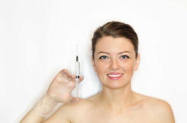 Schoonheid concept. mooie jonge vrouw met een perfecte huid, hand met een spuit voor injectie van botox, filler, hyaluronzuur. vecht tegen rimpels, veroudering. collageen applicatie
