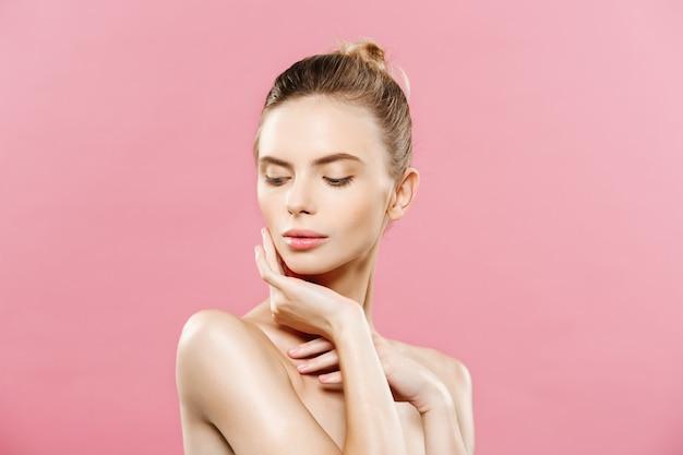 Schoonheid concept - mooie vrouw met schone verse huid close-up op roze studio. huidverzorging gezicht. cosmetologie.