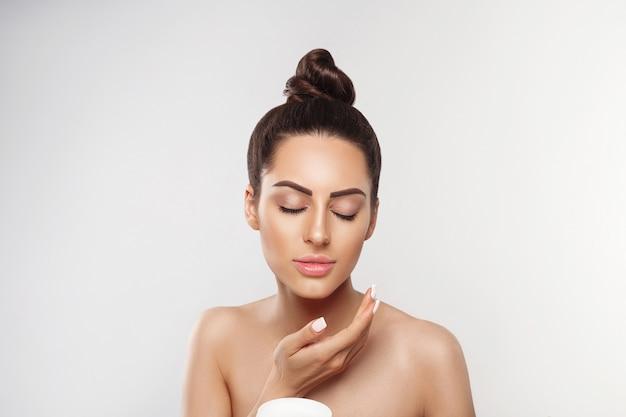 Schoonheid concept. vrouw cosmetica crème toe te passen en glimlachen