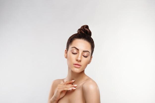 Schoonheid concept. vrouw die schoonheidsmiddelenroom toepast. het vrouwtje houdt een flescrème in haar hand en smeert het over haar schouder om haar huid te hydrateren.