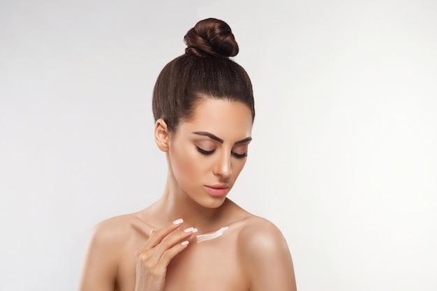 Schoonheid concept. vrouw houdt een cosmetische crème in haar hand en smeert deze op haar schouder om haar huid te hydrateren. vrouw crème toe te passen en glimlachen.