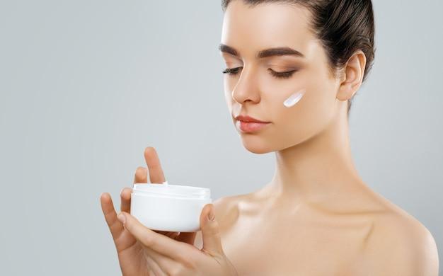 Schoonheid concept. vrouw houdt een vochtinbrengende crème in haar hand en verspreidt deze over haar gezicht om haar huid te hydrateren. huidsverzorging.