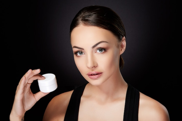 Schoonheid concept, vrouw met crème in de hand en camera kijken. hoofd en schouders van mooie jonge vrouw met gladde huid, zelfzorg. studio, zwarte achtergrond