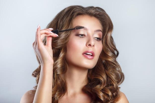 Schoonheid cosmetica. close-up van mooie sexy vrouw die zwarte mascara op lange dikke wimpers met borstel zet.