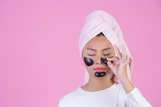 Schoonheid cosmetische peeling. jonge vrouw met zwarte peeling masker op huid cosmetische huidverzorging peeling product op het gezicht op een roze.