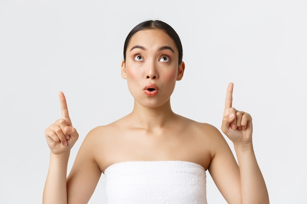 Schoonheid, cosmetologie en spa salon concept. verbaasd en onder de indruk van mooie aziatische vrouw in witte handdoek die geweldig aanbod ziet, vingers omhoog wijst en naar boven kijkt naar aankondiging, witte muur.