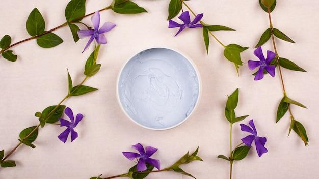 Schoonheid crème en violet bloemen plat lag, bovenaanzicht op witte achtergrond.