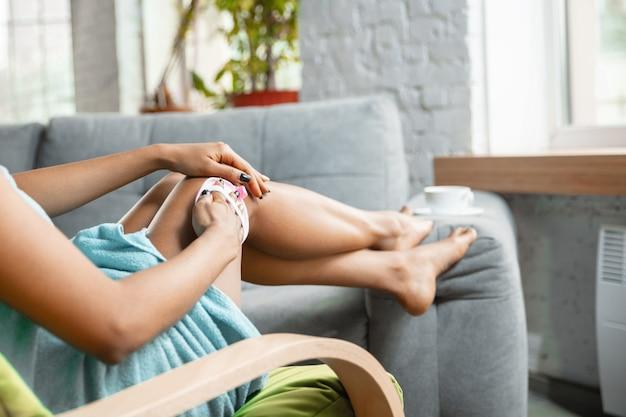Schoonheid dag. close up van afro-amerikaanse vrouw in handdoek doet haar dagelijkse schoonheidsroutine thuis. zittend op de bank, de huid van haar benen masserend. concept van schoonheid, zelfzorg, cosmetica, gezonde levensstijl.