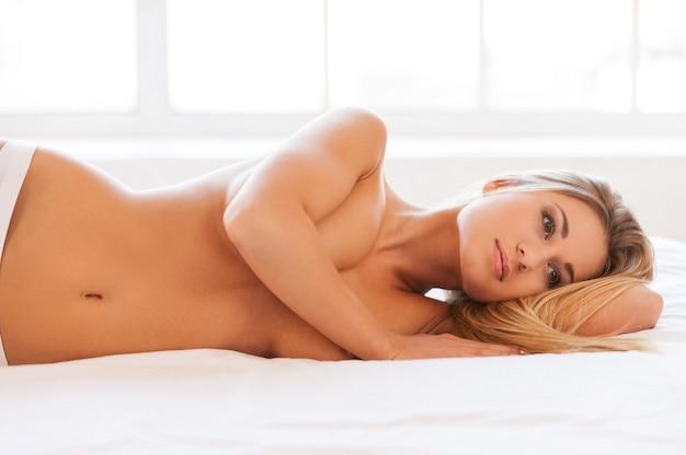 Schoonheid dag dromen. mooie jonge shirtless vrouw in slipje liggend in bed en borsten bedekken met hand