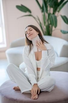 Schoonheid dag. jonge vrouw in het wit zittend op een ronde stoel met banden om haar nek