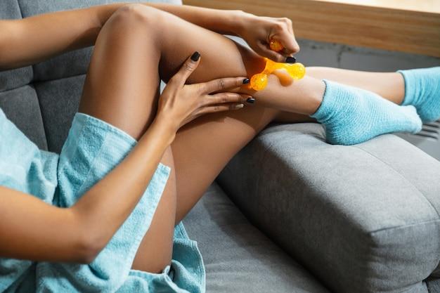 Schoonheid dag. sluit omhoog van vrouw die handdoek draagt die haar dagelijkse huidverzorgingsroutine thuis doet. zittend op de bank, de huid van de benen masseren met een cosmetische roller. concept van schoonheid, zelfzorg, cosmetica, jeugd.