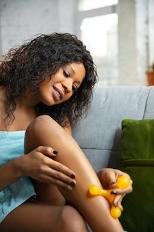 Schoonheid dag. vrouw die handdoek draagt die haar dagelijkse huidverzorgingsroutine thuis doet. zittend op de bank, de huid van de benen masserend met de roller van de cosmetica, glimlachend. concept van schoonheid, zelfzorg, cosmetica, jeugd.