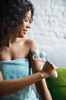 Schoonheid dag. vrouw die handdoek draagt die haar dagelijkse huidverzorgingsroutine thuis doet. zittend op de bank, de huid van de handen masserend met de roller van de cosmetica, glimlachend. concept van schoonheid, zelfzorg, cosmetica, jeugd.