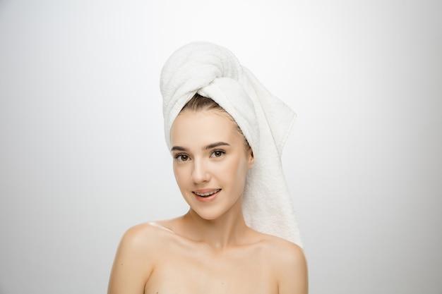 Schoonheid dag. vrouw die handdoek draagt die op witte studioachtergrond wordt geïsoleerd. dag voor zelfzorg, huidverzorging, schoonheidsroutine.