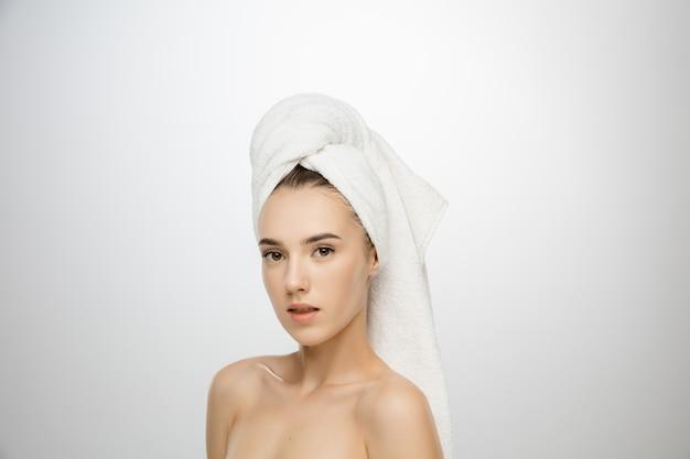 Schoonheid dag. vrouw die handdoek draagt die op witte studioachtergrond wordt geïsoleerd.