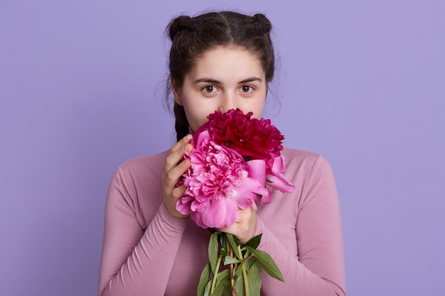 Schoonheid delicate vrouw ruikende lentebloemen en met charmante uitdrukking, dame met staartjes met bloemen geïsoleerd over lila muur.