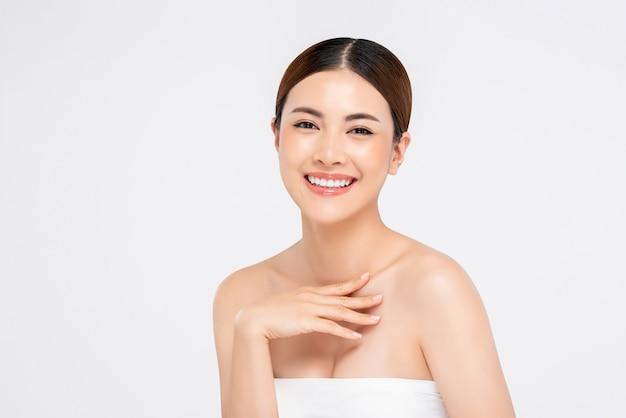 Schoonheid die van jeugdige heldere huid is ontsproten die vrij aziatische vrouw glimlacht