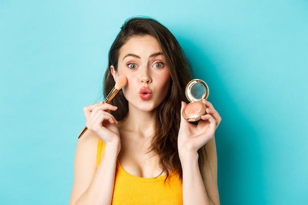 Schoonheid. domme glamour meisje tuit lippen, make-up met borstel toe te passen en bloost op camera te tonen, staande tegen een blauwe achtergrond.