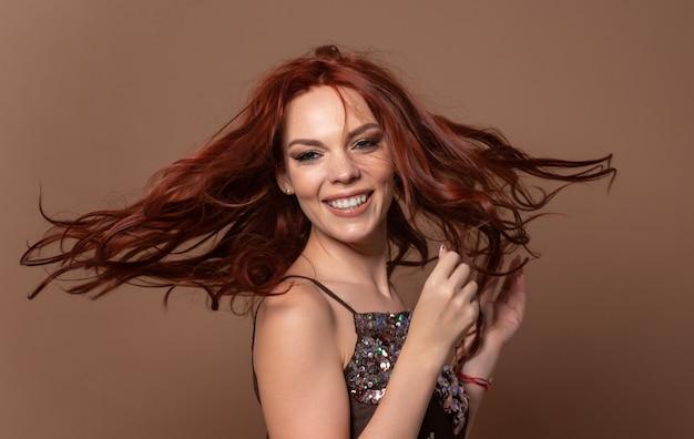 Schoonheid dynamisch portret van een roodharige gelukkige mooie vrouw op een beige achtergrond.