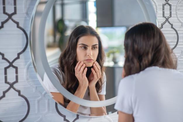 Schoonheid. een vrouw die haar spiegelbeeld in de spiegel bekijkt