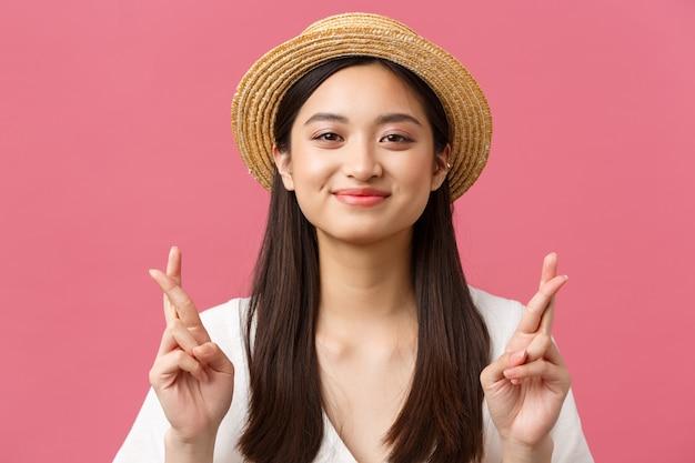 Schoonheid, emoties en vrije tijd en vakantie concept. close-up van een hoopvol dromerig aziatisch meisje dat een zomervakantie naar zee wenst, een strohoed draagt, veel geluk kruist en optimistisch glimlacht.