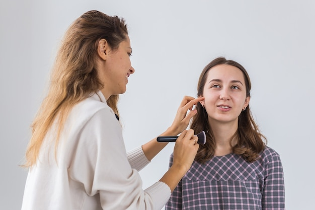 Schoonheid en cosmetica concept - make-up artiest professionele make-up van jonge vrouw doen