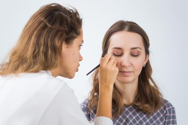 Schoonheid en cosmetica concept - make-up artist professionele make-up van jonge vrouw doen