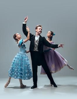 Schoonheid en gratie. mooie eigentijdse ballroomdansers die op grijze studioachtergrond worden geïsoleerd. sensuele professionele artiesten die wals, tango, slowfox en quickstep dansen. flexibel en gewichtloos.