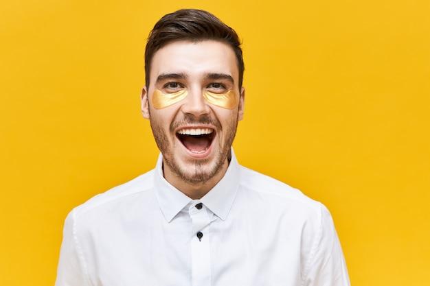Schoonheid en huidverzorging concept. foto van opgewonden, vrolijke jonge man met stoppels die gouden plekken onder de ogen draagt om er wakker en verfrist uit te zien, schreeuwend van opwinding, met wijd geopende mond