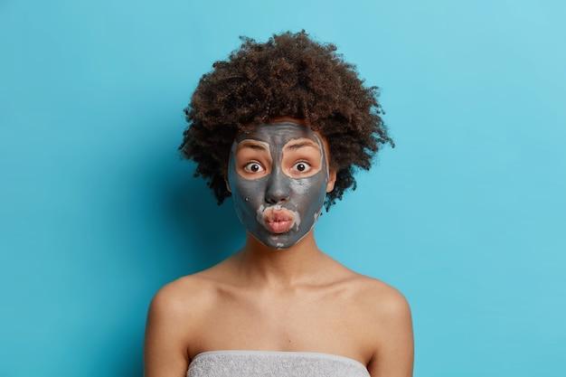 Schoonheid en huidverzorging concept. verrast afro-amerikaanse vrouw met krullend haar geldt voedende klei masker op gezicht geniet detox behandeling gewikkeld in badhanddoek toont blote schouders geïsoleerd op blauw