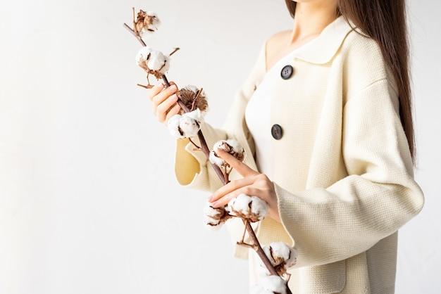 Schoonheid en jeugdconcept. mooie vrouw die in gezellige kleren tak van katoenen bloemen houdt